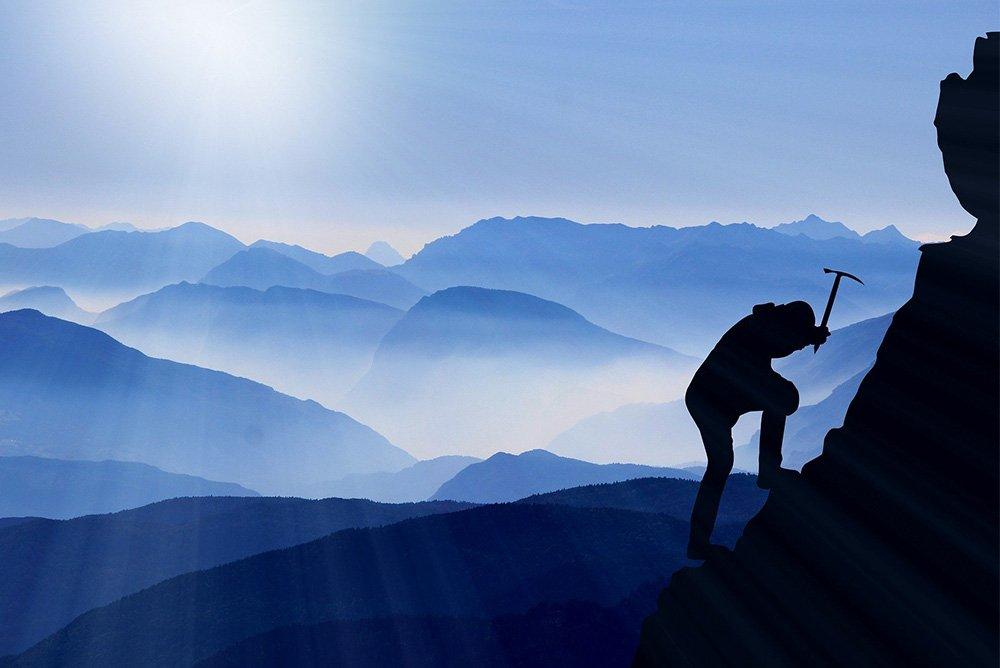 homme avec un piolet montant une montagne, le tout à contre jour