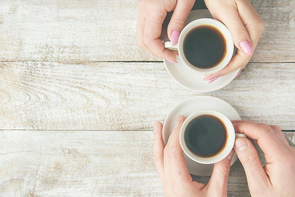 2 paires de mains tenant des tasses à cafés vu de haut